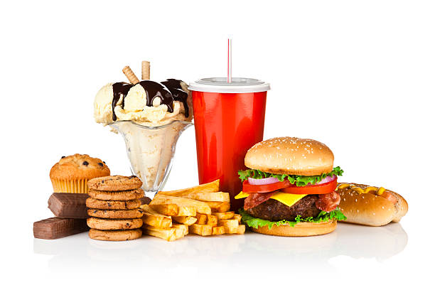 Unhealthy food isolated on white background Group of unhealthy food isolated on white background. The composition includes, candy bar, muffin, cookies, ice cream, french fries, a glass of soda, hamburger and a hot dog. This is an unhealthy food rich in carbohydrates, sugar and calories.  DSRL studio photo taken with Canon EOS 5D Mk II and Canon EF 70-200mm f/2.8L IS II USM Telephoto Zoom Lens unhealthy eating stock pictures, royalty-free photos & images