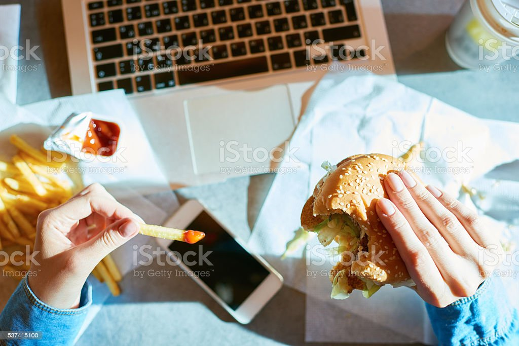Unhealthy lunch Female hands holding bitten hamburger and dipped French fries Adult Stock Photo