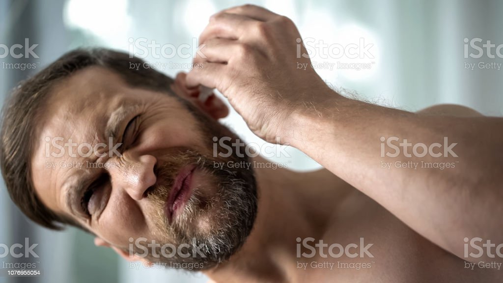 Unhealthy male dripping ear drops, bacterial infection...
