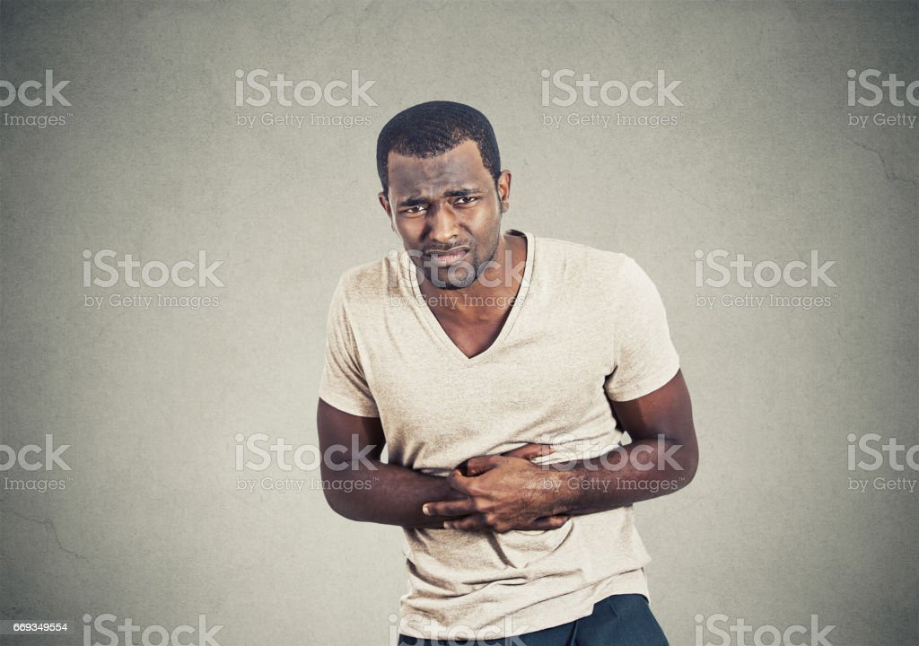 Unhealthy man, doubling over in stomach pain looking sick unwell miserable ill, stock photo