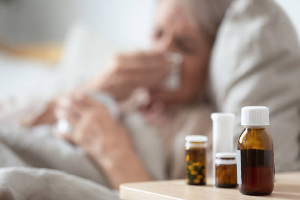 unhealthy mature woman suffering from cold, meds on bedside table - prescription meds stock pictures, royalty-free photos & images