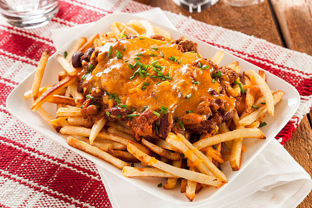 Unhealthy Messy Chili Cheese Fries Unhealthy Messy Chili Cheese Fries on a Background chili con carne stock pictures, royalty-free photos & images