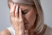 istock Unhealthy middle aged sad woman touching forehead. 1251350038