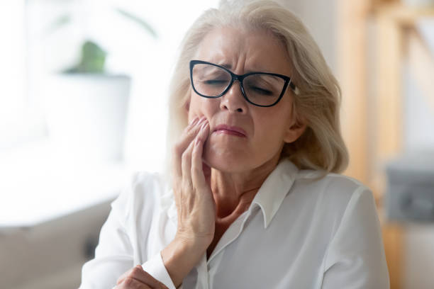 unhealthy senior woman touch cheek suffering from toothache - mouth imagens e fotografias de stock