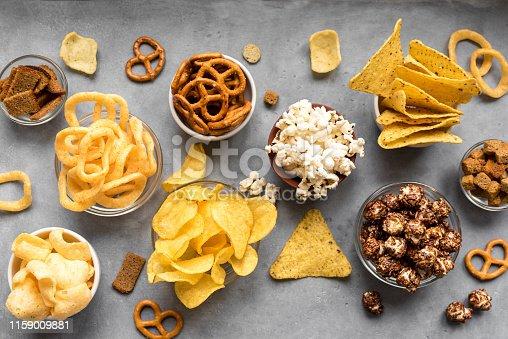 Assortment of Unhealthy Snacks: chips, popcorn, nachos, pretzels, onion rings in bowls, top view, copy space. Unhealthy eating concept.