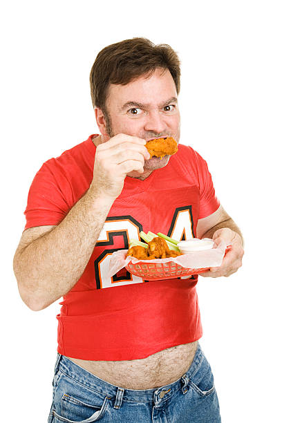 Unhealthy Stadium Food Overweight middle aged man in tight football jersey, chowing down on fried chicken wings.  Isolated on white.  men in tight jeans stock pictures, royalty-free photos & images