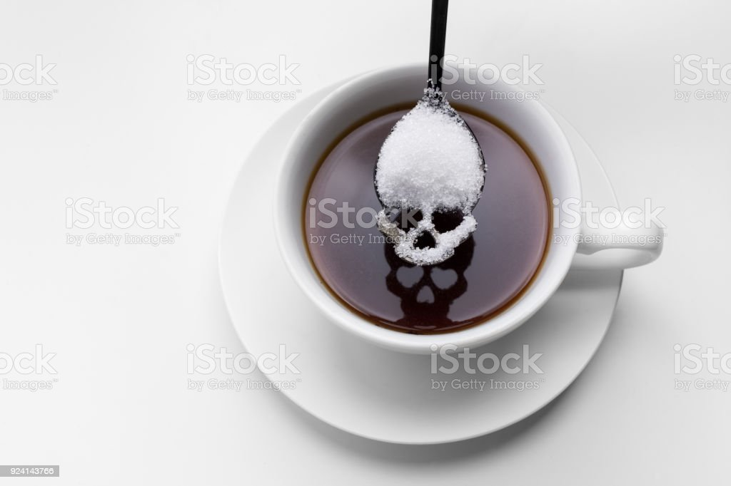 unhealthy white sugar concept. Scull spoon with sugar and cup of black coffee royalty-free stock photo