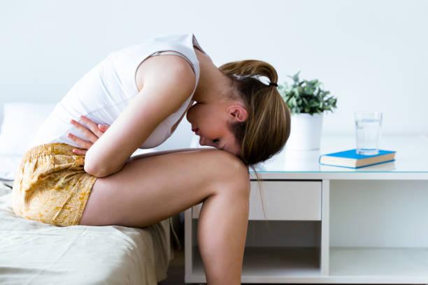 jovem saudável com dor de estômago apoiando-se na cama em casa. - abdome - fotografias e filmes do acervo