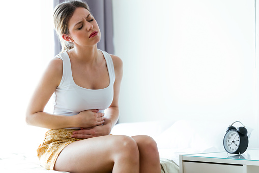istock Unhealthy young woman with stomachache leaning on the couch at home. 943133110