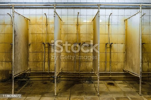 Unhygienic public showers room. Wet, mold, rusty ceramic tiles wall.