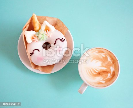 Unicorn donut with coffee on blue background. Top view. Flat lay