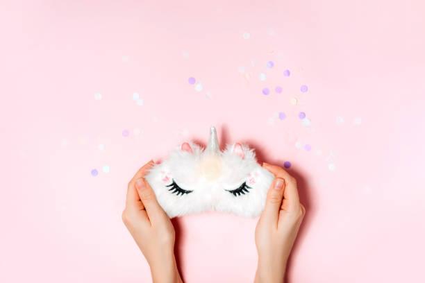 unicorn sleep mask in girls hand. - unicorn bed imagens e fotografias de stock