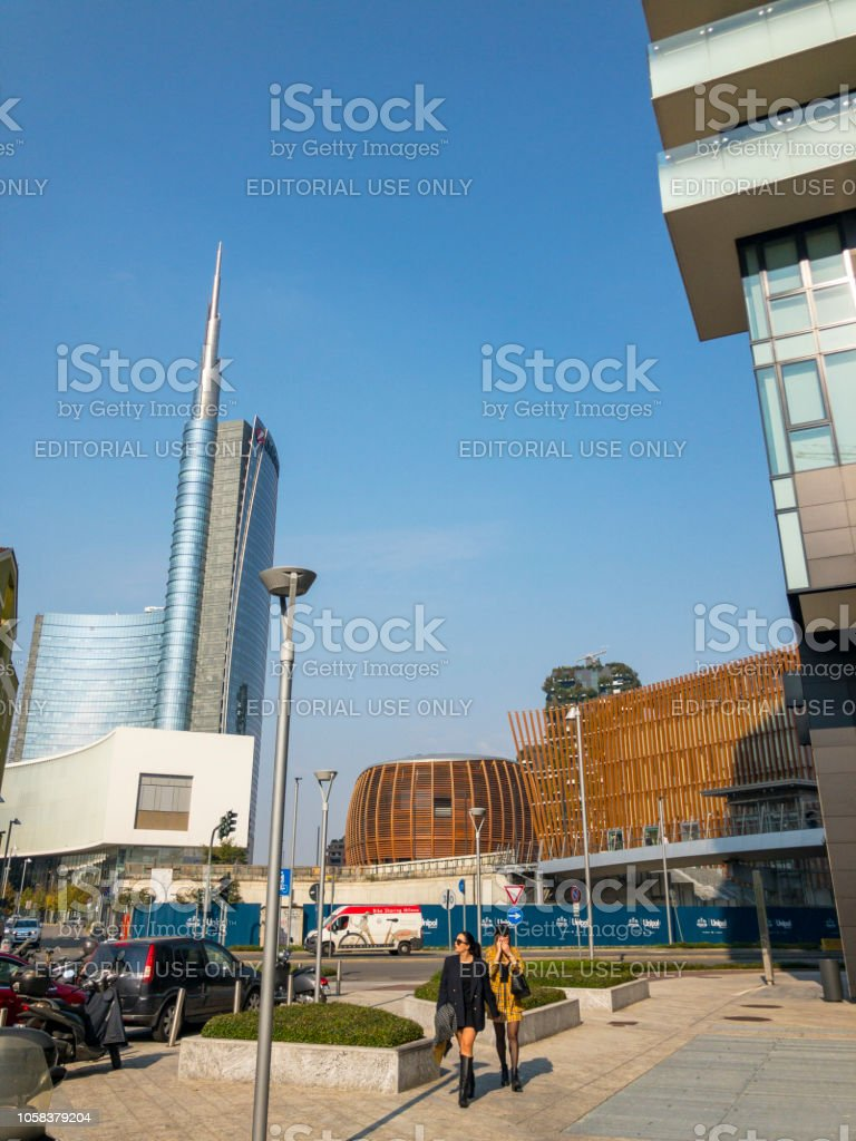 Unicredit Tower, seen from Via Amerigo Vespucci, Milan, Italy. Fashionable girls strolling through the center of Milan. Models. Women in business - foto stock