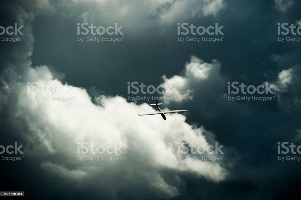 Unidentifiable acrobatic glider gliding across the cloudy sky - foto stock