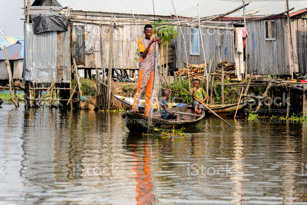 Unidentified Beninese Man Cathes Fish With A Net In A Wooden Boat In
