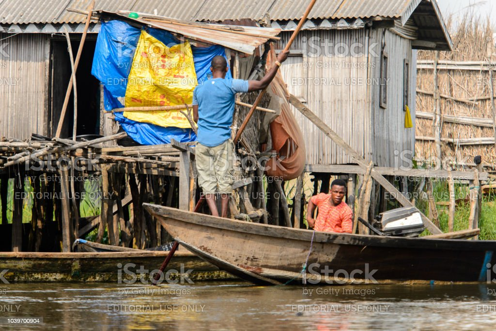 Unidentified Beninese Man Sails In A Wooden Boat In A Village Over