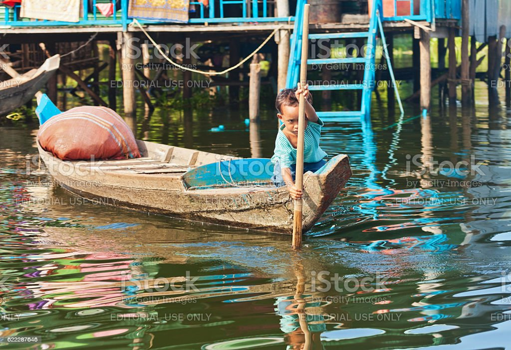 unidentified boy on a boat floating on Tonle Sap lake stock photo