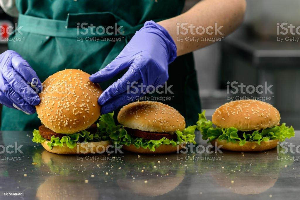 Unidentified chef preparing appetizing burgers stock photo