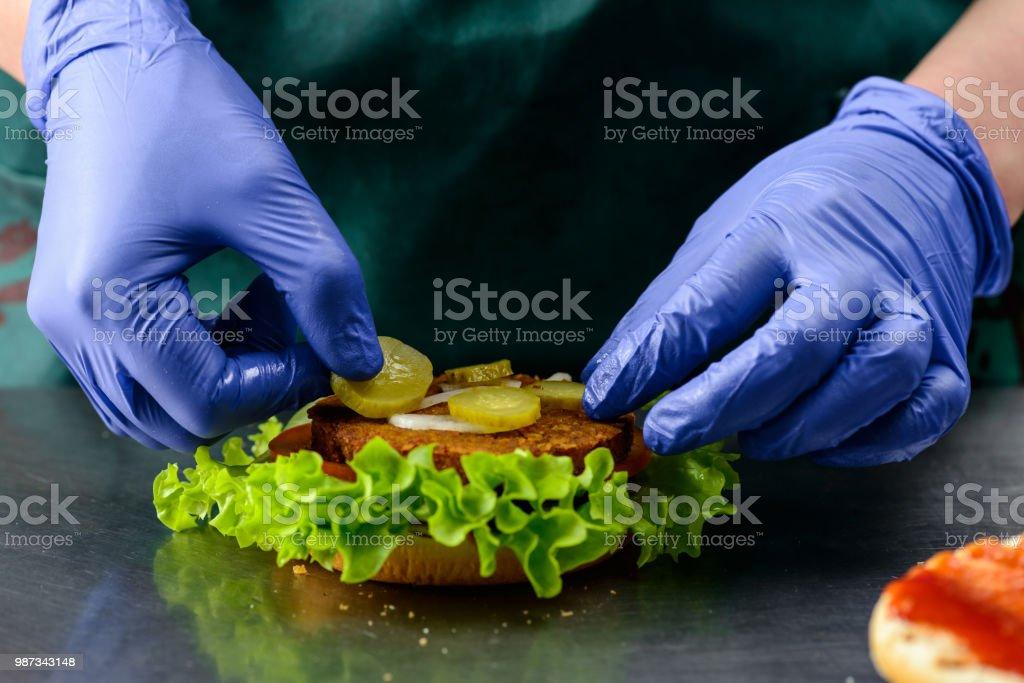 Unidentified chef preparing delicious juicy burger stock photo