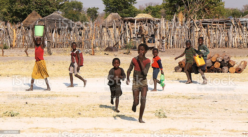 Unidentified children fetching water in a small village foto