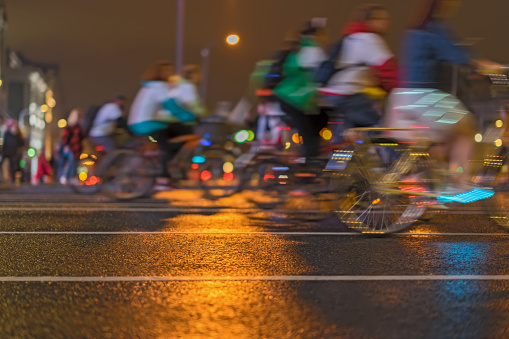 929609038 istock photo Unidentified colorful riding bicycle during at night on city street, abstract, motion blur, for background 948683872