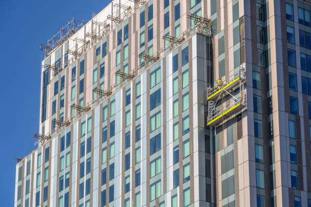 Unidentified construction workers on suspended scaffolding inspecting / installing cladding on a high rise building in London stock photo