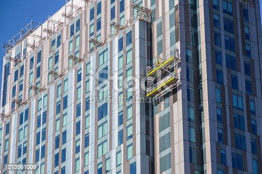 Unidentified construction workers on suspended scaffolding inspecting / installing cladding on a high rise building in London, England, UK