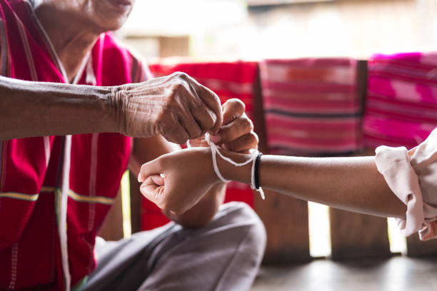 unidentified elder man from karen ethnic hill tribe minority tie guest's wrist for blessing in tying ceremony - minority stock photos and pictures