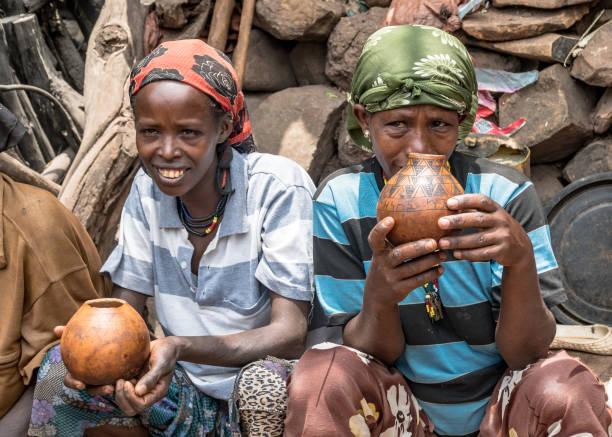 Unidentified Ethiopian women chatting and drinking in their village. Omo, Ethiopia - September 2017: Unidentified Ethiopian women chatting and drinking in their village. mercato stock pictures, royalty-free photos & images