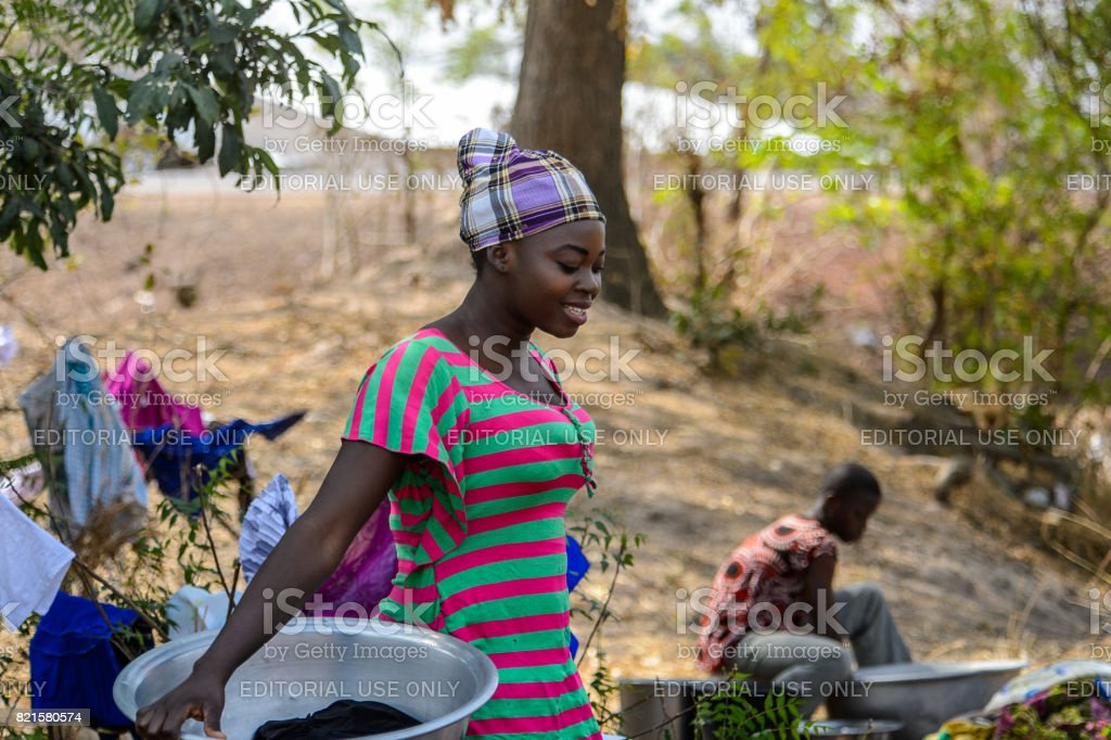 TECHIMAN, GHANA - JAN 15, 2017: Unidentified Ghanaian woman carries a basin on the Washing Day, which is every Sunday stock photo