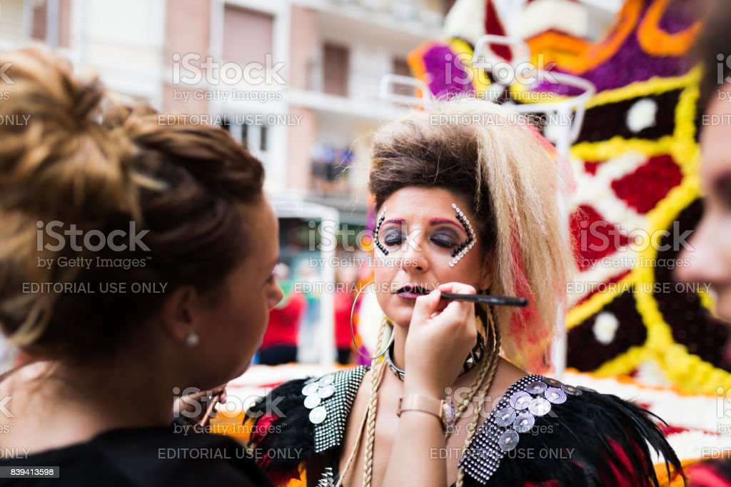 Unidentified girls receive the latest makeup tweaks before the parade of floats in the battle of flowers of Laredo, Cantabria, Spain stock photo