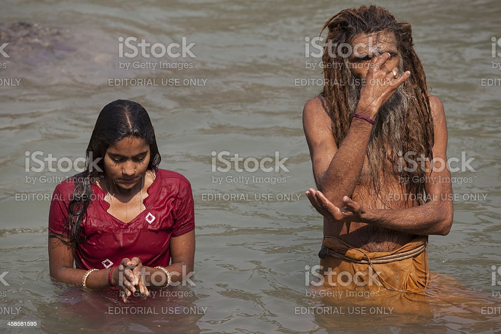 0c61673686c Unidentified hindu man and woman baths in holy Ganges River - Stock image .