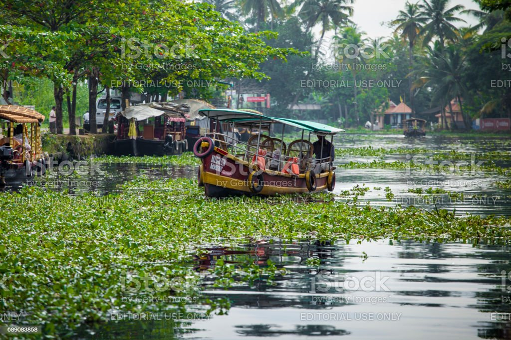 Unidentified indian people in small boat in backwaters. stock photo