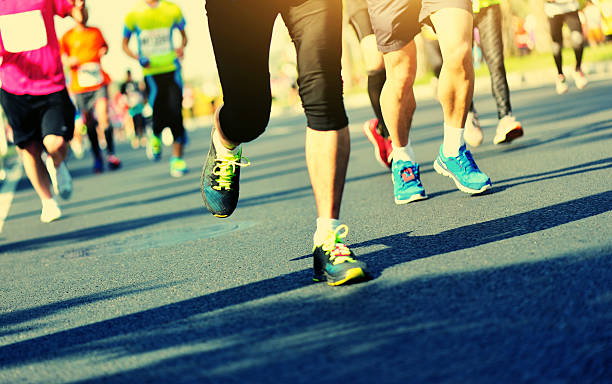 unidentified marathon athletes legs running on city road - marathon stock photos and pictures