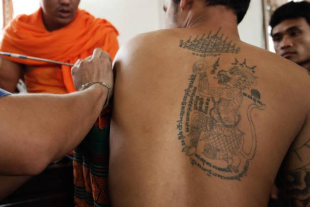 unbekannter meister machen thai traditionelle tätowierung (yantra) auf körpereigene anhänger während gedenkfeier master tag wat bang pra, thailand. - buddhist tattoos stock-fotos und bilder