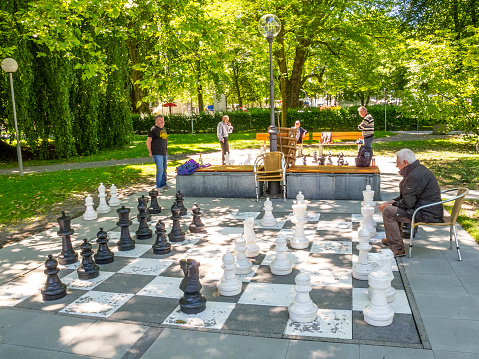 Unidentified men play chess with giant chess pieces on the Lake Constance, Bodensee promenade in Bregenz, Austria