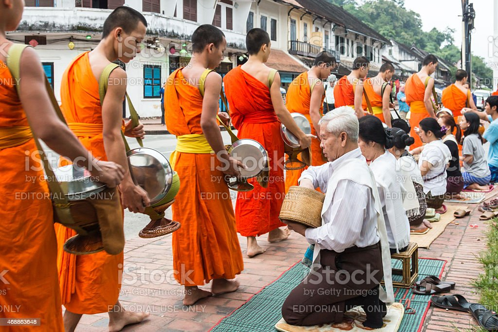 Unidentified monks walk to collect alms and offerings stock photo