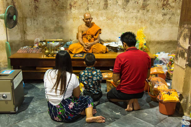 unidentified name family to merit the blessings from buddhist monks in church of wat yai suwannaram temple in phetchaburi, thailand - religious celebration stock photos and pictures