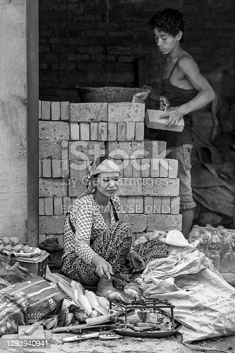 Unidentified nepalese woman cooking corn on the cob and unidentified nepalese man building a wall with bricks in the streets of Kathmandu, Nepal