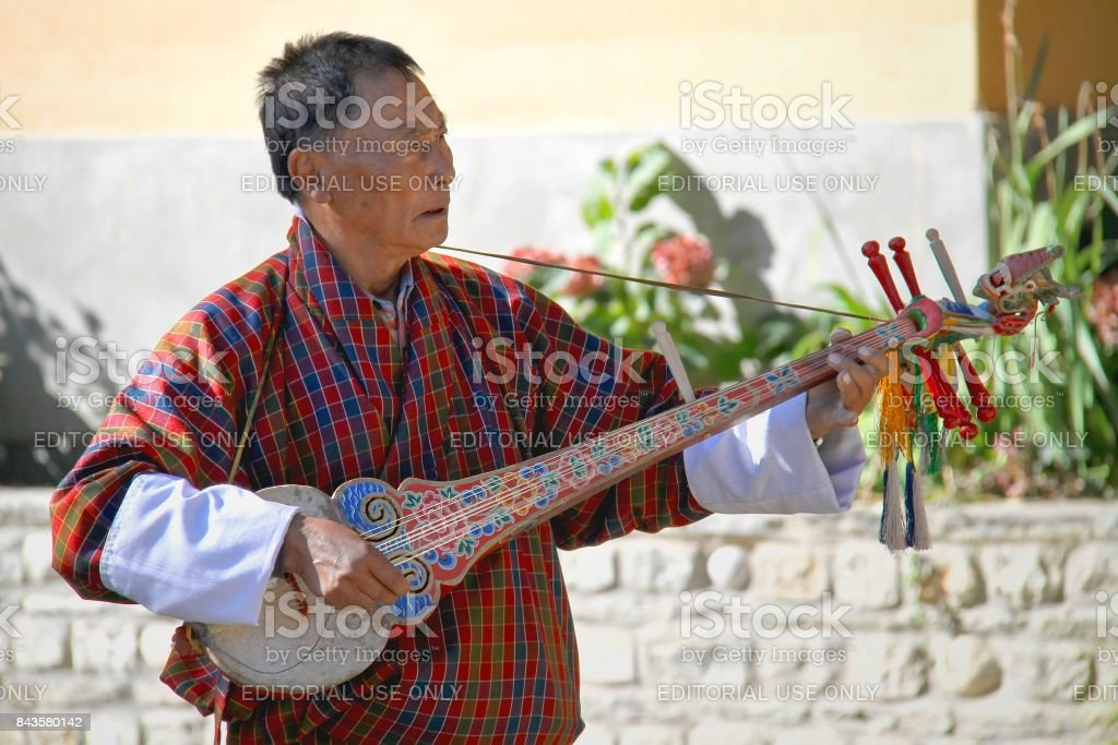Unidentified old man musician in traditional dress (Gho) playing Dramnyen instrument at hotel in Paro, Bhutan stock photo