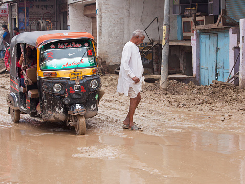 Uttar Pradesh, India – March 3, 2015: An unidentified pedestrian risks an imminent soaking negotiating traffic on an unsurfaced village road in the aftermath of torrential rain