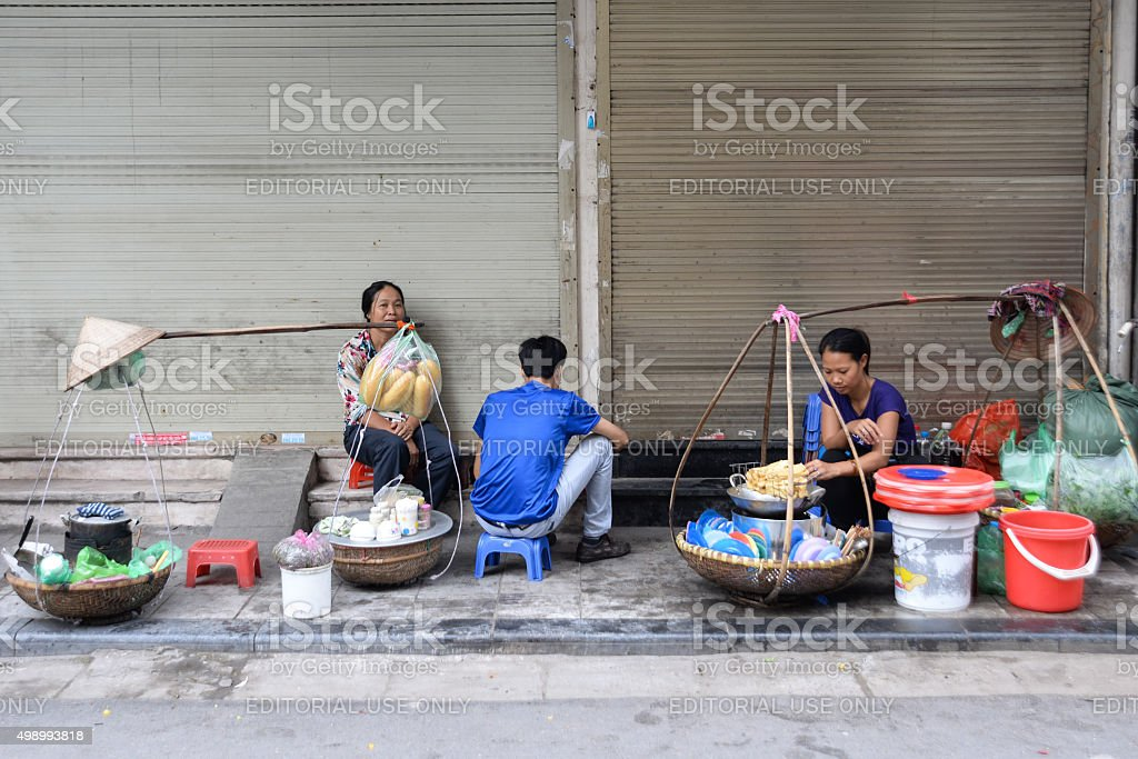 Unidentified people eat food on street in Hanoi, Vietnam stock photo