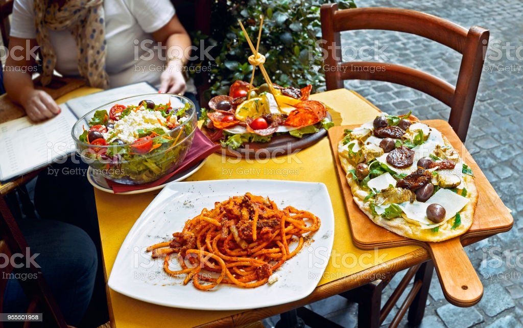 Unidentified people eating traditional italian food in outdoor restaurant stock photo
