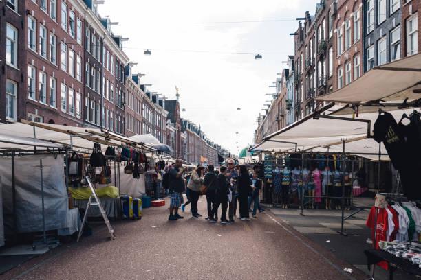 unidentified people in street market in oude pijp neighborhood in amsterdam a cloudy day of summer - günstig nach amsterdam stock-fotos und bilder