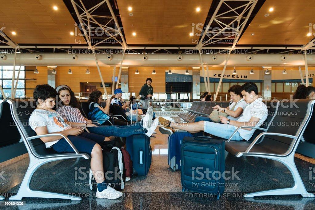 Salon d'inconnus en attente dans la porte d'embarquement à l'aéroport - Photo