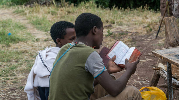 Unidentified pilgrim reading bible at one of the old rock churches from Lalibela stock photo