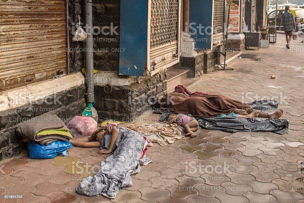 Unidentified  poor people sleep at the street in Mumbai stock photo