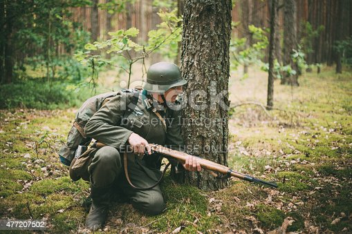istock Unidentified re-enactor dressed as German soldier aiming a rifle 477207502