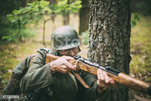 istock Unidentified re-enactor dressed as German soldier aiming a rifle 477207504