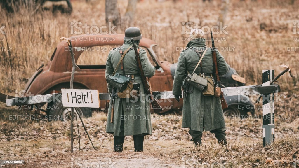 Unidentified Re-enactors Dressed As German Infantry Wehrmacht soldier at World War II are on patrol in autumn field. stock photo